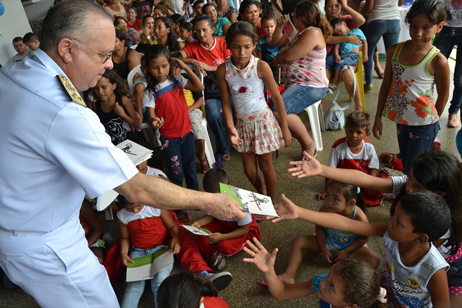 Vice-Almirante Savio distribuindo cartilhas às crianças