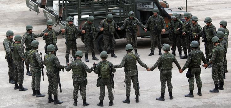Militares da Força de Pacificação da Maré em momento de oração antes de patrulhamento nas ruas da comunidade