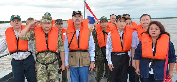 Ministro da Defesa do Brasil, Aldo Rebelo, e seu colega paraguaio, Diógenes Martínez, durante toque de silêncio a bordo de um navio da armada do Paraguai