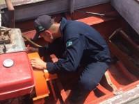 Militar da CPAOR instalando cobertura de eixo em embarcação regional